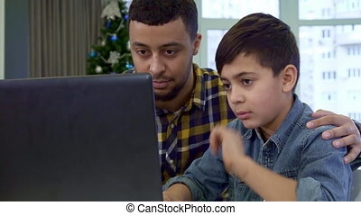 Father and son waving at the laptop
