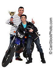 Father and son with a motorbike trophy