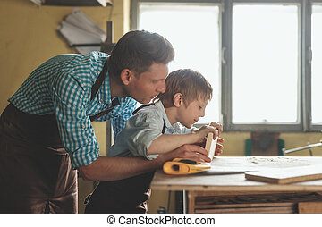 Father and son with a wooden plank