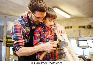 father and son with ax and wood plank at workshop - family, ...