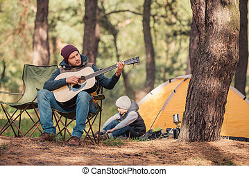 father and son with guitar in forest