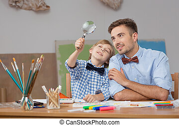Father and son with magnifier