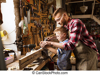 father and son with plane shaving wood at workshop