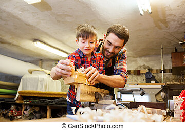 father and son with plane shaving wood at workshop - family...
