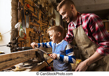 father and son with rasp working at workshop - family, ...