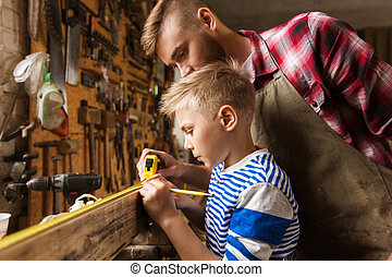father and son with ruler measure wood at workshop - family,...