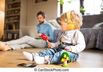 Father and son with smartphone, earphones and laptop.