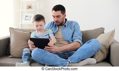 father and son with tablet pc playing at home - family,...