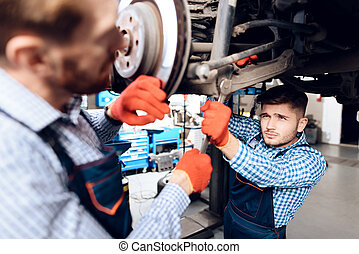 Father and son work at the auto service. Two mechanics work with the details of the car.
