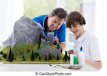 Father and son work on model building project - Father and...