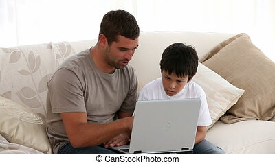 father and son working on laptop