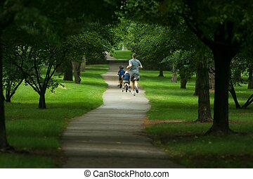 father jogging and two sons biking on path in city park
