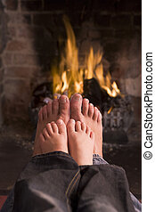 Father and son\'s feet warming at a fireplace