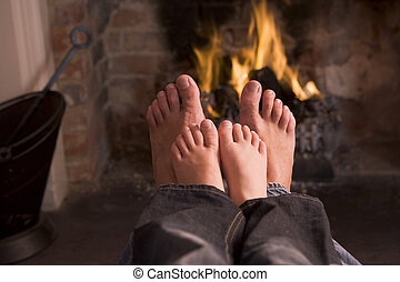 Father and son\\\'s Feet warming at a fireplace