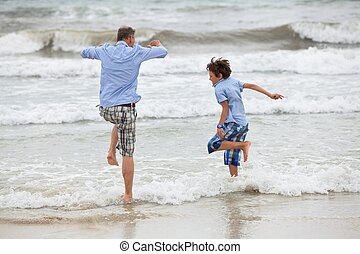father and sons on the beach playing in the sand holiday family