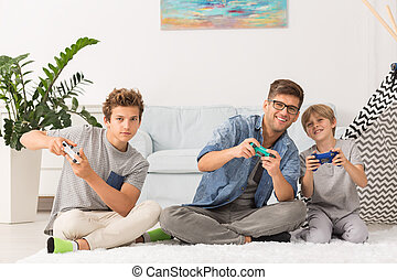 Father and sons playing video games