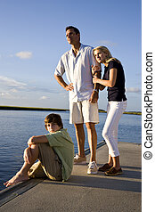 Father and teenage children on dock by water