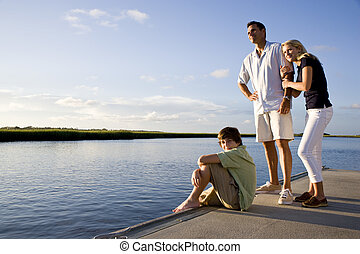 Father and teenage children on dock by water enjoying sunny...