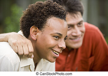 Father and teenage son - African American teenage boy with...