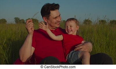 Joyful affectionate father seated on beanbag chair on meadow holding laughing adorable toddler daughter, having fun together, enjoying summer vacations in countryside in rays of setting sun,