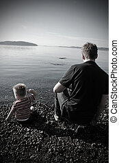 Father and toddler son sitting on a pebbly beach throwing rocks in the water