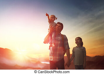 Father and two children at sunset