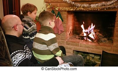 Father and two son sitting by fireplace