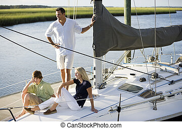 Father and two teenage children relaxing on boat - Family...