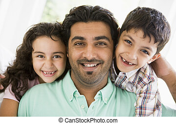 Father and two young children in living room smiling (high key)