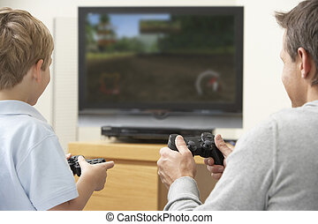 Father And Young Son Playing With Game Console -