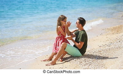 Father applying sun cream to daughter nose. - Young father...