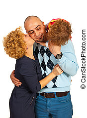 Father being kissed by wife and daughter