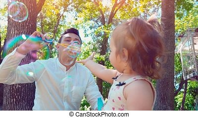 Father blowing soap bubbles and little daughter catches them in the park, lifestyle family concept
