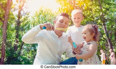 Father blowing soap bubbles for son and little daughter in the park, lifestyle family concept