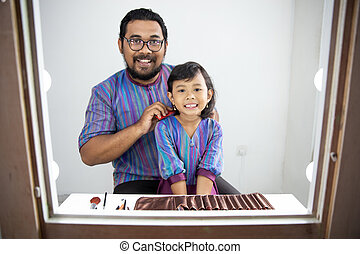 father brush his daughter's hair