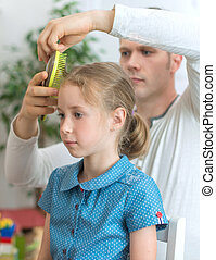 Father brushing hair of his daughter.