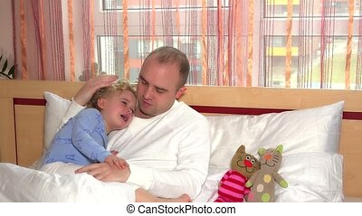 Father calm down his crying little daughter lying in white bed