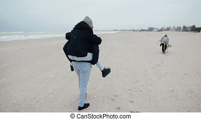 Father carries a daughter on her back. happy family on a walk on the beach