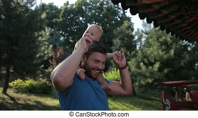 Father carrying cute baby boy on shoulders in park