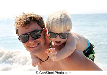 Father Carrying Happy Child on Piggy Back on Beach by Ocean