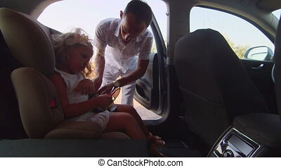 Father carrying his little daughter by car in child safety booster seat