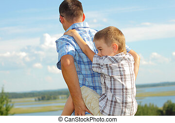 Father carrying his son piggyback. Blue sky on the background. Portrait of smiling father giving his son piggyback ride outdoors