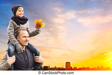 father carrying son with autumn leaves in city