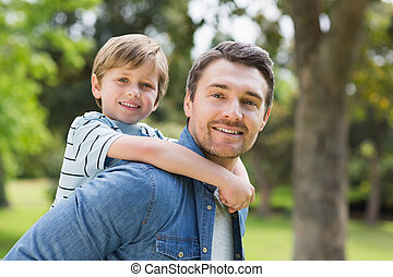 Father carrying young boy on back at park - Side view...