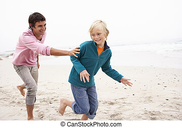 Father Chasing Son Along Winter Beach