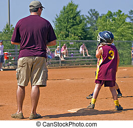 Father Coaching Daughter's Softball - A man standing with...