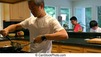 Father cooking food while his sons playing in the background 4k