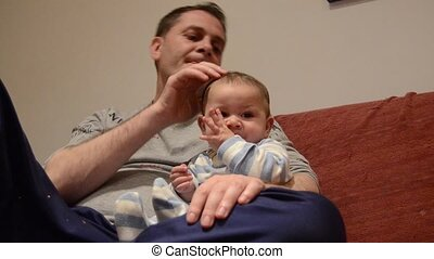 Father cuddling his six months old baby boy whille watching...