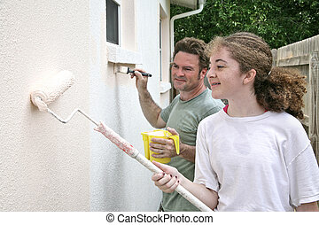 A horizontal view of a father and daughter painting their house together.