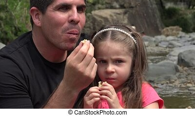 Father Daughter Snacking At River